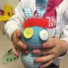 Child and a sock animal made in a craft workshop